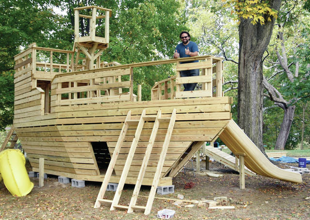 Josh Lurie of Troy stands on the bow of a birthday gift that he is building in his back yard for his daughters.