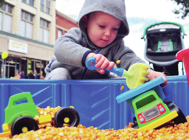 Reiley Robinson, 2, of Piqua plays in a corn box during Saturday's Mainstreet Piqua Fall Fest in the downtown.