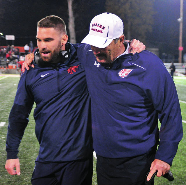 Piqua High School assistant football coach Travis Nees (left) congratulates his dad, Piqua head coach Bill Nees folllowing Friday's win over Tippecanoe. It was his 200th career win.