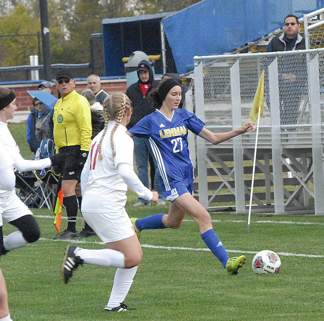 Rob Kiser|Miami Valley Today Lehman Catholic's Agnes Schmiesing sends the ball downfield against Indian Lake as Kyleigh Huffer closes in.