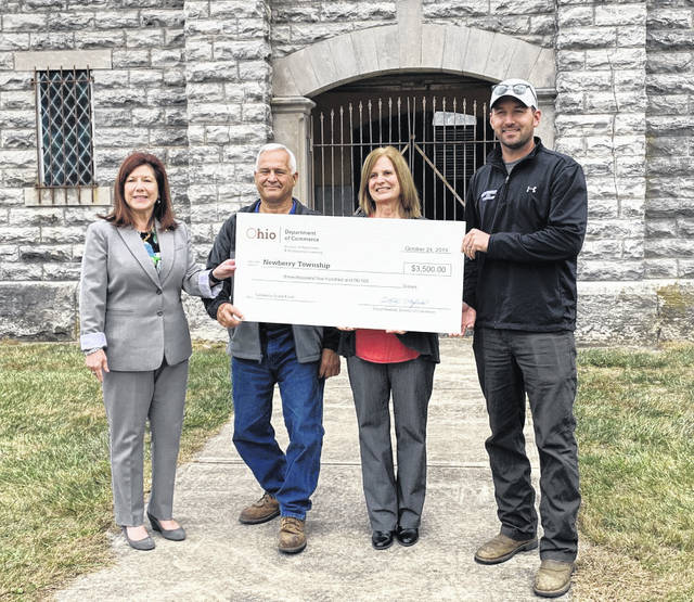 Ohio Department of Commerce representative Anne Petit, left, presents a $3,500 check to Newberry Township trustee Mike Maniaci, Newberry Township fiscal officer Mary Beth Benedict, and Newberry Township Superintendent Tyler Moore. The money is part of a state-wide cemetery grant fund and will go toward mausoleum repairs.