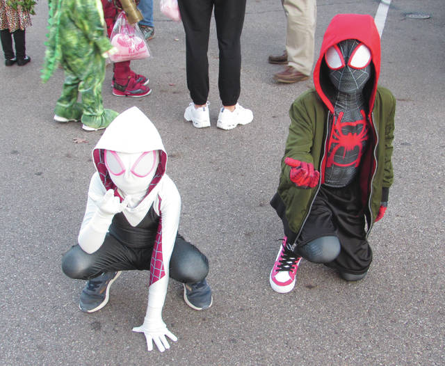 Sam Wildow | Miami Valley Sunday News Raegan Ashton (left) and Tyler Ashton (right), each of Piqua, are Spider-Gwen and Spider-Man at the 63rd annual Piqua Kiwanis Halloween Contest Parade on Wednesday, Oct. 23, outside of the Piqua Public Library.