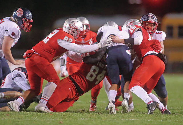 Lee Woolery | Miami Valley Today Troy's Tito Fuentes (82), Colby Harris (84) and Brayden Siler (15) stop a Piqua ballcarriers during Friday night's Trojan victory at Troy Memorial Stadium.