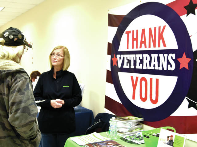 Gaye Szabo of Humana Health chats with a veteran at the Miami County Health Department in Troy on Friday during the annual Veterans Health Fair. Representatives from numerous veterans care organizations were present to assist with questions and concerns. Also, health screenings were available, as well as lunch.
