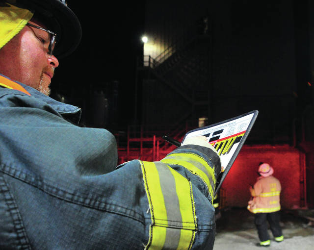 Covington firefighter Jim Drieling mans the status board during a Tuesday evening fire at PBM on Hazel Street in Covington.