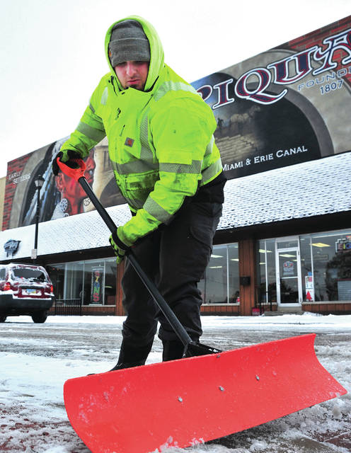 Piqua city employee Hunter Bryant shovels some of the first snowfall of the season from the sidewalks in downtown Piqua on Tuesday morning.