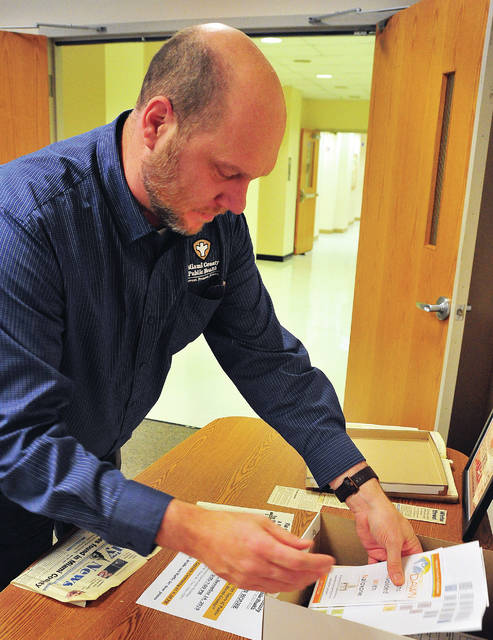 Miami County Health Commissioner Dennis Propes places items into a time capsule during a Thursday afternoon open house celebrating the 100th anniversary of the Miami County Health Department.