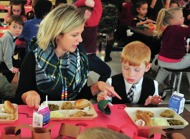 First-grade teacher Stephanie Friend, assists Own Schulz, in learning dining etiquette during Tuesday's Formal Dining Thanksgiving Dinner at Springcreek Elementary School. Students at Springcreek, Washington, and Piqua Central Intermediate schools were treated to the annual formal dinner before students are dismissed for Thanksgiving break.