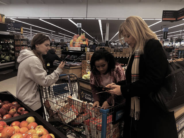 From left, Sienna Mader, 13, Alivia Worth, 14, and student council adviser Angie Clouser, count boxes of stuffing mix at the Troy Walmart on Monday. Troy Junior High School's staff and students raised funds to provide 25 families with a full Thanksgiving dinner and food staples. It's been a tradition at the school for more than 30 years. Troy Fish and Game provided each family a turkey as part of the school's fundraiser.
