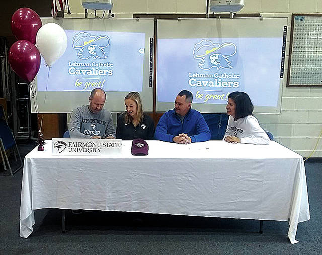 Rob Kiser|Miami Valley Today Lehman Catholic senior Ava Behr signed her lettr of intent to play soccer for Fairmont State. From the left are her father Kevin, Ava, Lehman Catholic coach Jeremy Lorenzo and her mother Nikki.