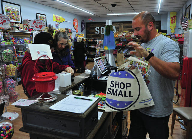This & That's Candy on Main owner Tom Lillicrap, right, assists customers on Saturday during the Small Business Saturday event in Piqua sponsored by Mainstreet Piqua.
