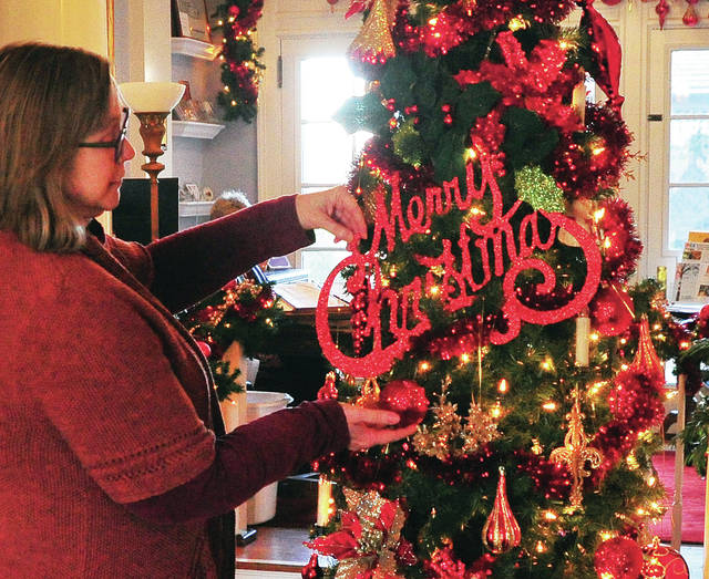 "Leona Sargent, exhibit coordinator for the Troy-Hayner Cultural Center, puts the finishing touches on decorations as the center prepares to open their Christmas decoration display this weekend. The center's Children's Day, with Santa Claus, refreshments, a puppet show and arts and crafts will be offered from 1-5 p.m. Saturday at the center. The Troy-Hayner Cultural Center will then offer its annual open house grand opening, featuring holiday decor throughout the 11-room house from 1-5 p.m. Sunday. This year's theme is ""Contemporary Christmas."" The grand opening features tours, live music and refreshments. The holiday exhibit will then continue through Jan. 5. Learn more at TroyHayner.org."