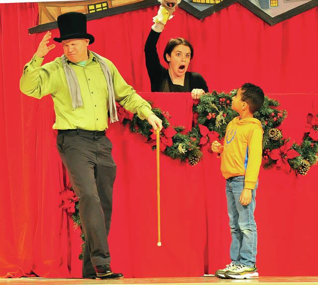 "Vincent Wenrick, right, a kindergarten student at Washington Primary School in Piqua, assists actors from Madcap Puppets of Cincinnati in their rendition of Charles Dickens,<em> </em>""A Christmas Carol,"" at the school on Wednesday. <em></em>"