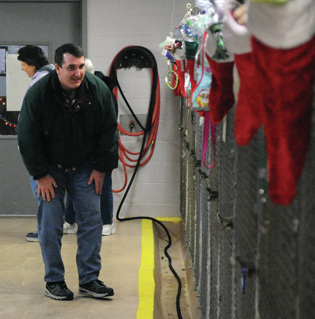 Stan Strohmenger of Piqua checks out some of the dogs available for adoption at the Miami County Animal Shelter. Strohmenger stopped by to donate to the shelter's Stockings program and couldn't resist saying hello to the dogs while visiting.