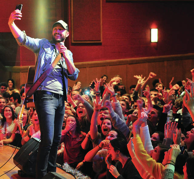 Country music performer Drew Baldridge uses a student's cell phone to take a group selfie during Wednesday's K99.1 music concert at Troy High School. Troy students won the country music station's recent Gold-out T-shirt selling contest to beat childhood cancer. Proceeds go to benefit Dayton Children's Medical Center.