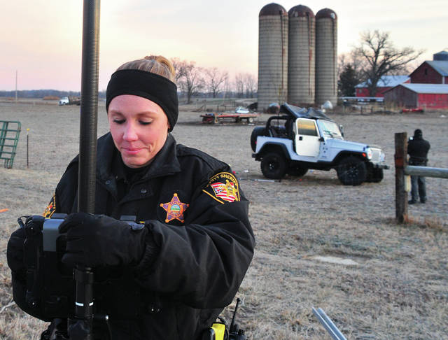 Deputy Bonnie McMaken works as part of the Miami County Sheriff's Department crash reconstruction team at the scene of a Friday morning fatal crash on State Route 202 near Fulton Farms.