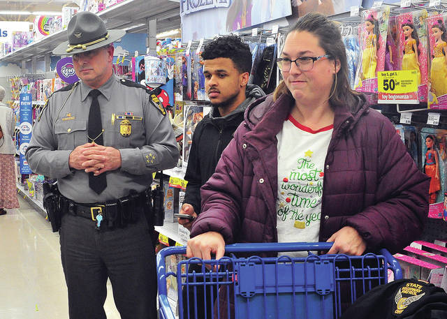 Lt. Joe Gebhart of the Piqua Post of the Ohio State Highway Patrol and Douglas Townsell, son of an OSHP dispatcher, assist Jodi Fosnight of Piqua in some Christmas shopping at the Troy Meijer Store on Friday during the annual COPs shopping night sponsored by the Miami County FOP and Miami County Victim Witness.