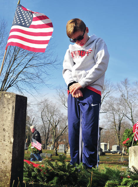 Grady Stillwell, 10, offers a personal moment of silence and prayer at the grave of a Piqua veteran at Forest Hill Cemetery on Saturday. Stillwell, a member of the Piqua Braves baseball club, was one of many local kids and adults who turned out for the annual Wreathes Across America event. More than 700 wreathes were placed on the graves of veterans.