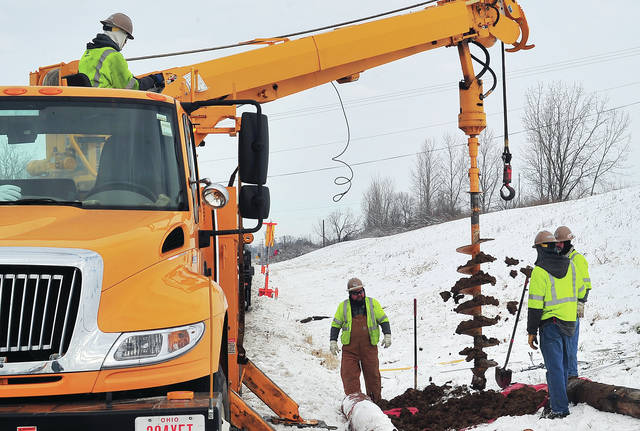 Crews from Piqua Power work in the snow and cold on Tuesday to replace a power pole and electric lines on Piqua-Troy Road following a Monday morning crash that took out a pole knocking out power to portions ot the city.