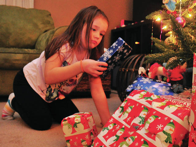 Della, 6, checks out one of the gifts that Santa left under her Christmas Tree during the Miami County FOP and Victim Witness gift delivery on Dec. 18.