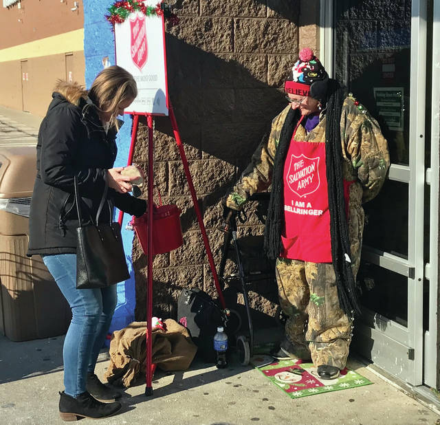 Bell ringer Sheryl Kolker of Gettysburg watches as a contribution is made to the 2019 Salvation Army Kettle Campaign at the Troy Walmart on Thursday. Kolker has been volunteering as a Salvation Army bell ringer for the past four years.