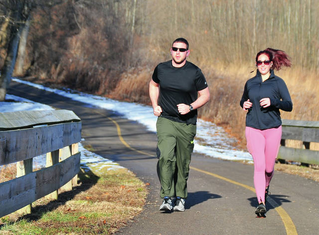 Cody and Haley Lavy of Bradford go for a post-Christmas run on the paths at the Miami County Park District's Farrington Reserve on Thursday.