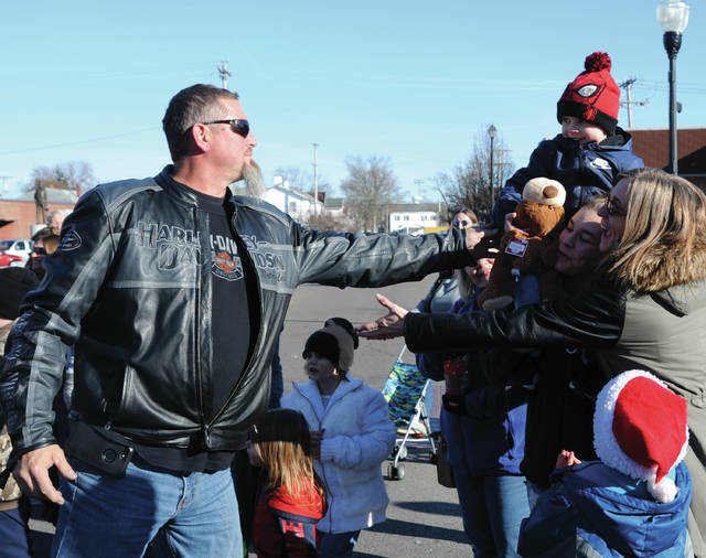 Brian Emerick of Piqua got off his motorcycle to hand a stuffed animal to a young parade viewer during Saturday's Downtown Christmas Parade in Piqua. More than 70 motorcycle riders participated in the event.