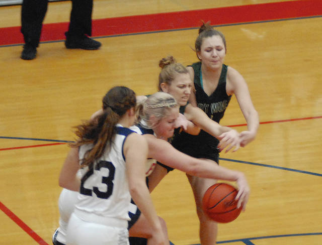 Rob Kiser|Miami Valley Today Piqua's Aubree Schrubb grabs a loose ball against Greenville as Kenzi Anderson looks on.