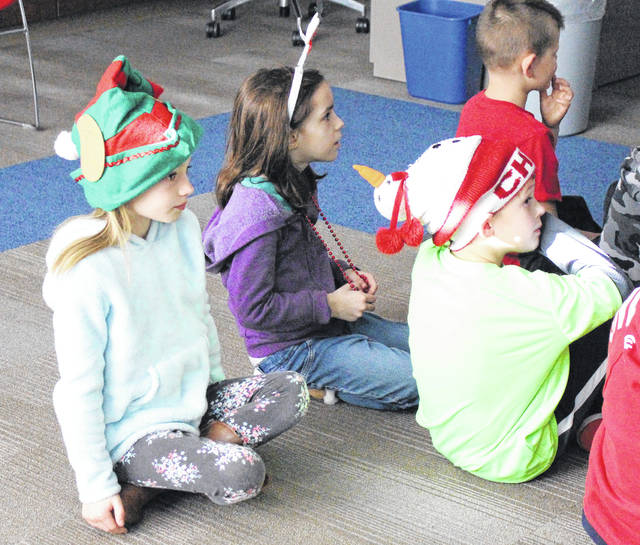 Washington Primary second-graders Giulianna Krommanecker, left, daughter of Abigail Seipel and Chance Krommanecker, sits alongside fellow second-graders Leah Swabb, middle, daughter of Angie and Rodney Swabb, and Lucas Streib, son of Barbara and Matt Streib, during the music segment of Thursday's Read-A-Thon. The students, clad in Christmas-themed accessories, were waiting patiently for the next song to play.
