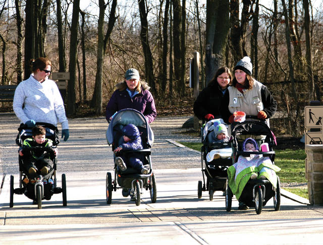 Left to right, Marizel Mihal, along with her son Lachlan, 2; Leighann McCulla, her son Kayden, 2; Posey Culdertson with her daughter, Luna, 1; and Amy Cost, along with her son Winston, 21 months, participate in a Moms and Tots hike at the Miami County Park District's Charleston Falls on Monday. Culdertson, a Miami County Park District naturalist, was leading the hike. ©2020 Miami Valley Today. All rights reserved.
