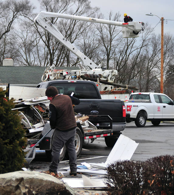 Levi Long, rakes and removes debris from the parking lot at Baird Funeral Home as power crews, background, repair and replace power poles in the area following a Saturday evening tornado that touched down in Troy.