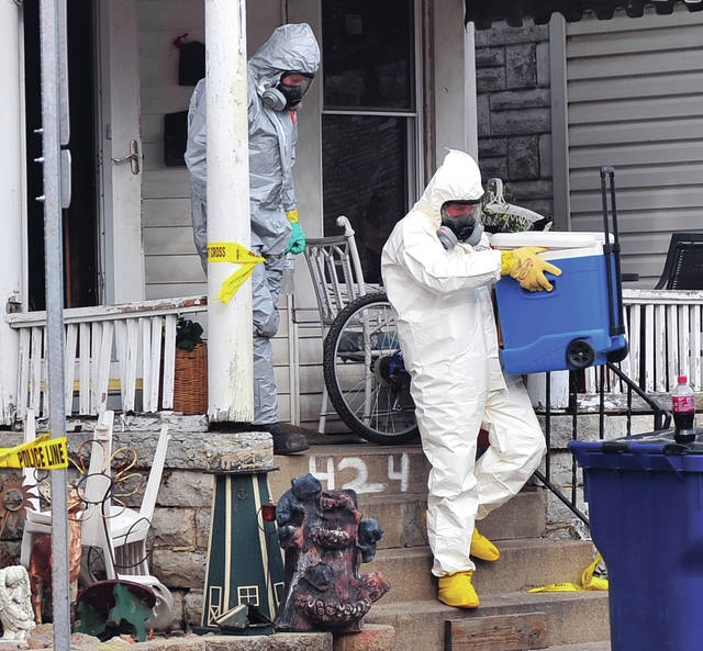 Investigators from Ohio BCI remove evidence from a home at 424 West High Street in Piqua on Friday afternoon following the execution of a drug-related search warrant.