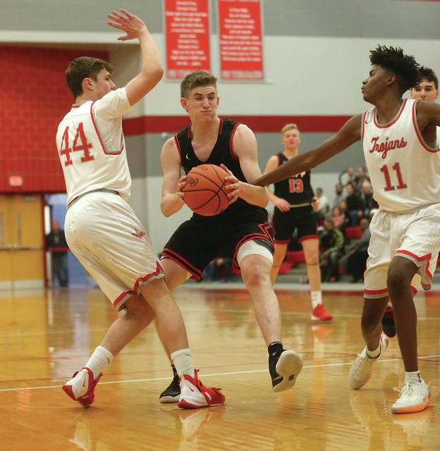 Lee Woolery | Miami Valley Today Tippecanoe's Zach Frederick brings the ball up the floor as Troy's Tre Archie (11) and Charlie Walker (44) defend Tuesday at the Trojan Activities Center.