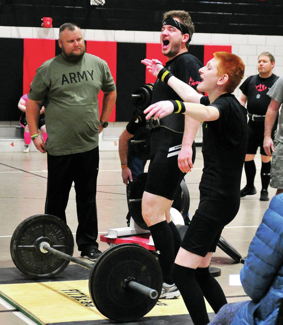 Eric Anderson, left, a US Army veteran and volunteer, watches as Caleb Karnehm celebrates a successful deadlift while teammate Stephen Stewart joins in the celebration, during Saturday's Miami County Board of Developmental Disabilities, also known as Riverside, powerlifting tournament at Riverside.