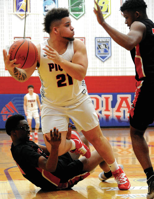 Piqua's Jerell Lewis, 21, passes off to a teammate as he is tripped by West Carrollton's Aigbokhai Kadari Friday night at Garbry Gymnasium.