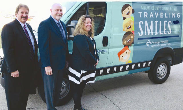 Provided photo Left to right, Tim Snider, Chief Operating Officer of UVMC, Tom Parker, president of UVMC, and Stephanie M. Silk, executive director of the Miami County Dental Clinic, stand with the new Traveling Smiles van.