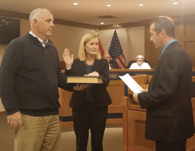Kathryn Huffman (center) with her husband Steve Huffman (left) as she takes the oath of office being administered by Miami County Municipal Court Sam Huffman (right) after being appointed to the Tipp City Council.