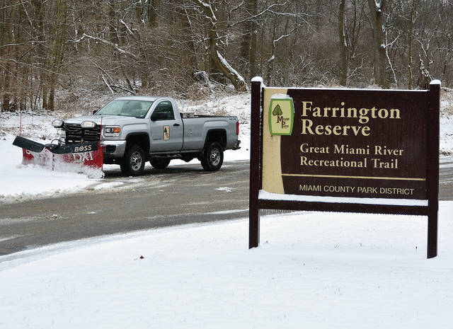 Miami County Park District officials work to clear snow from the Farrington Reserve on Friday morning so that park visitors can enjoy the recreational trails following a snowfall.