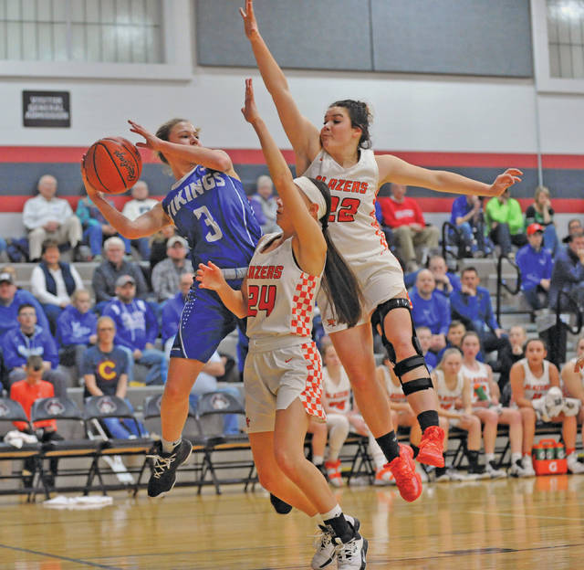 Josh Brown | Miami Valley Today Miami East's Paxton Hunley looks to pass around a pair of National Trail defenders during Thursday's Division III sectional tournament game at Covington High School.