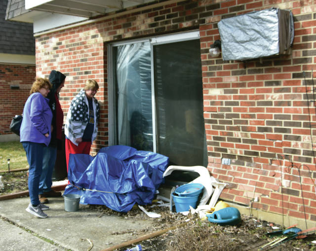 Residents of an apartment building on Imperial Court in Troy check the damage to their building after a vehicle crashed into the structure shortly after 2 p.m. on Sunday. The vehicle fled the scene. The Miami County Engineer's Office was called in to evaluate possible structural damage to the building. No injuries were reported.