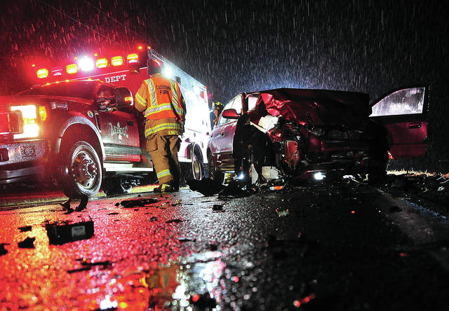 Troy Fire Department medics along with firefighters from Troy and Casstown work at the scene of a head-on crash on Troy-Urbana Road near Casstown-Sidney Road on Monday evening.