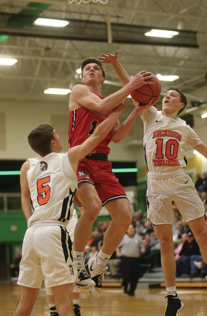 Lee Woolery | Miami Valley Today Milton-Union's Nathan Brumbaugh splits an Arcanum double-team on his way to the basket during a Division III sectional tournament game Tuesday at Northmont High School.