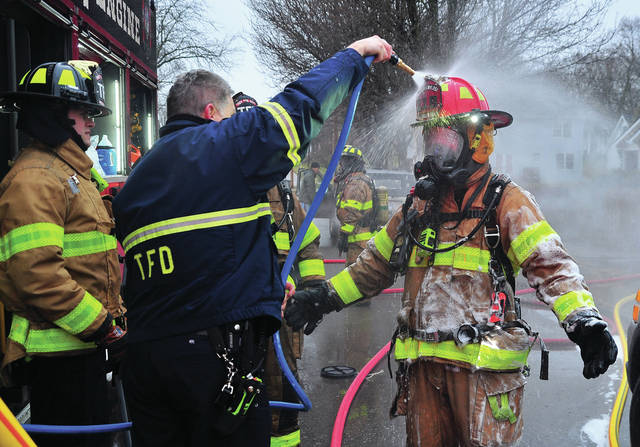 Troy firefighter Luke Lindeman looks on as Jeff Shelton hoses off Don Pemberton to remove potential contaminants as they conclude fighting a Wednesday morning fire on Drury Lane in Troy.