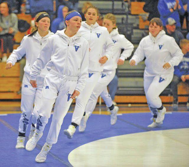 Josh Brown | Miami Valley Today file Olivia Shore leads the Miami East girls wrestling team out onto the mat before its historic dual against Olentangy Orange in December at Miami East High School. The match was the first all-girls dual in Ohio wrestling history.