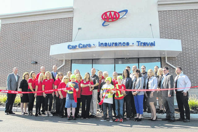 AAA Troy Car Care, Insurance and Travel Center leadership, community dignitaries and Troy Area Chamber of Commerce members, along with associates, officially cut the ribbon for the new AAA location.