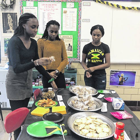 From left, Troy High School freshmen students Nailah Dbamba, Saidah Dbamba and Johnae Malcolm share their family's culture of Jamaica with Culture Club students. Each month, students share traditional food, dress and customs of their country with others. Nailah shares coconut drop cookies with the after-school club last month.
