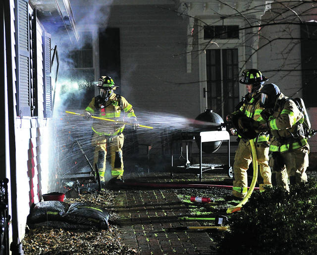 Firefighters from Troy work to extinguish a fire in the 300 block of S. Plum Street on Sunday evening.