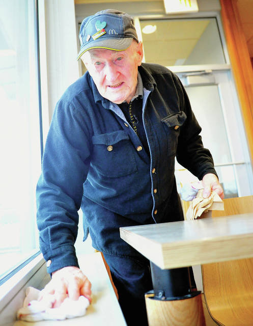 Hugh Ruppert, 88, of Pleasant Hill keeps the dining room of the Piqua McDonald's East location spotless during his Monday shift.