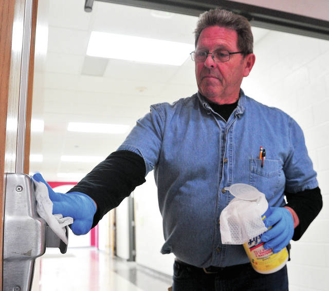Bryce Baker disinfects panic bars on doors at Newton High School on Thursday as part of the school system's ongoing battle to keep students from becoming ill.