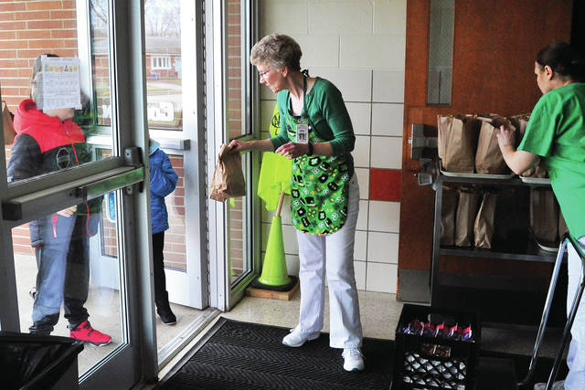 Lunchroom staff members Sharon Myers, center, and Nancy Myers, right, hand out lunches and breakfasts to students at the door at Cookson Elementary School on Tuesday. All Troy City Schools locations will be distributing lunches to students each weekday between 11:30 a.m. and 12:30 p.m. during the mandated school closure.
